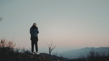 a woman standing on a mountaintop in early morning