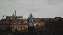 a woman with a backpack with a view of an ancient European city