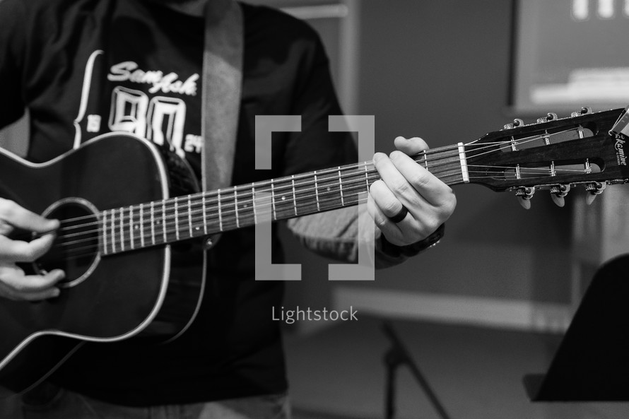 teen boy playing an acoustic guitar