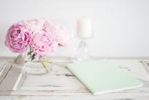 peonies, votive candle, vase, flowers, journals, pencil, table