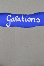Galatians - torn open kraft paper over intense blue paper with the name of the letter from Paul to the Galations
