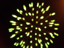 Green fireworks exploding in the night sky.