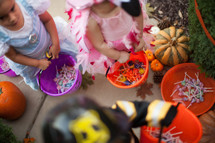 children trick or treating on a neighborhood sidewalk on Halloween
