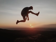 Silhouette of man leaping over a canyon at sunset.