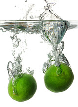 Limes submerged into water creating a splash.