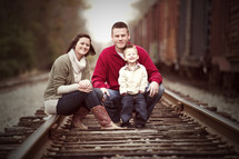 family sitting on railroad tracks