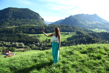 a woman standing at the top of a grassy hill