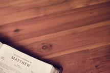 BIble on a wood floor opened to Matthew