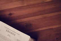 BIble on a wood floor opened to Exodus