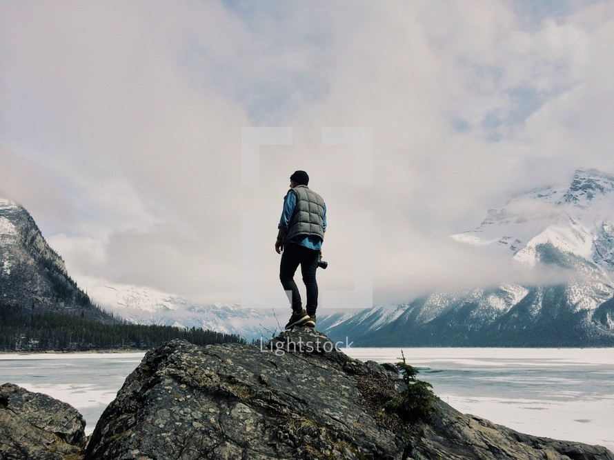 man standing on a rock hill by a lake surrounded by snow covered mountains