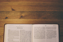 Bible on a wooden table open to the book of Titus.