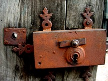 Lock and key of an old gated door that is rusty and weather beaten.