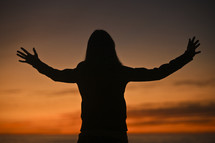 A woman with arms outstretched.