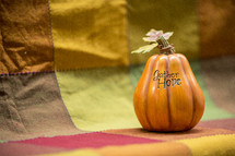 words GATHER HOPE on a pumpkin