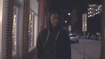 a man walking down a sidewalk alone at night