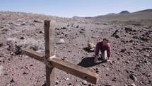 a man kneeling in front of a cross in a desert