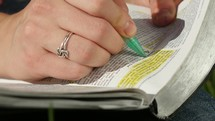 Hand highlighting a passage in the Bible.