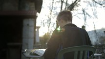 a man sitting outdoors at a table reading a Bible