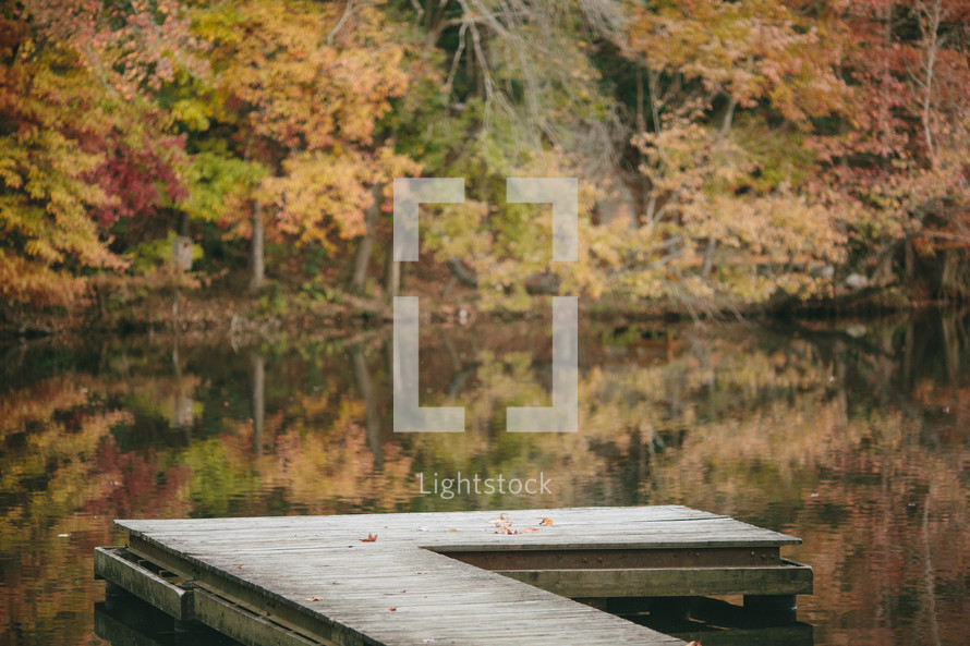 Empty dock with Fall colors over a lake