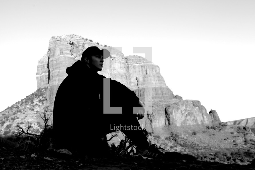 silhouette of man sitting in front of a mountain peak