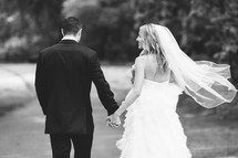 bride and groom walking holding hands outdoors