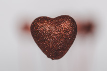 red glittery heart and blurry background