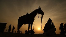 horse, tribesmen, and video production crew at sunset