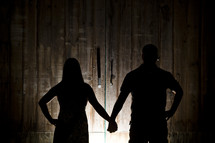 silhouette of a man and woman standing holding hands in a barn
