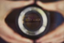Hands holding a camera lens reflecting Holy Bible.