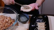 Folding Chinese pork dumplings.