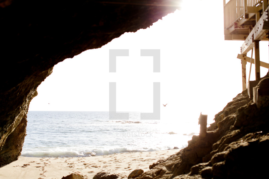 view of the ocean and beach from a cave