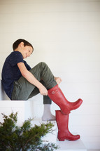kid putting on rain boots