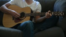 a young man sitting on a couch playing a guitar