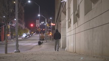 a man walking on a city sidewalk alone at night
