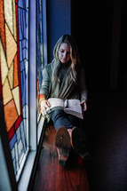 a woman reading a Bible in the window sill of a churches stain glass window