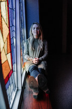 a woman sitting in the window sill of a stained glass window praying