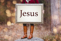 a woman holding a sign the reads Jesus