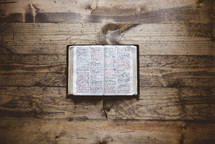 opened Bible on a wood background