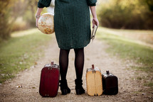 a woman holding a globe and Bible standing next to luggage