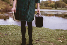 a woman with a Bible and suitcase