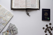 map, passport, Bible, coins, and cash on a white background