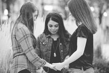 women holding hands in a prayer circle