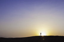 silhouette on a man in the desert at sunset