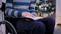 Christian man in wheelchair reading the Bible in front of Christmas tree. Spiritual time and studying the Bible concept. Dolly shot 4k closeup