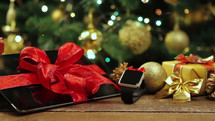 Tablet pc, smartphone and smartwatch with gifts and decorations in front of Christmas tree with lights on wooden table.