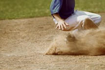 a boy sliding in baseball