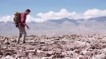 a man hiking through a desert landscape