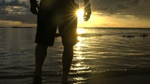man walking on a beach in shallow water
