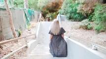 a woman in a flowing dress walking down steps