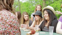 Girls laughing and sharing at a picnic table outside.